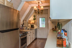 galley kitchen with white base cabinets and brown wood flooring