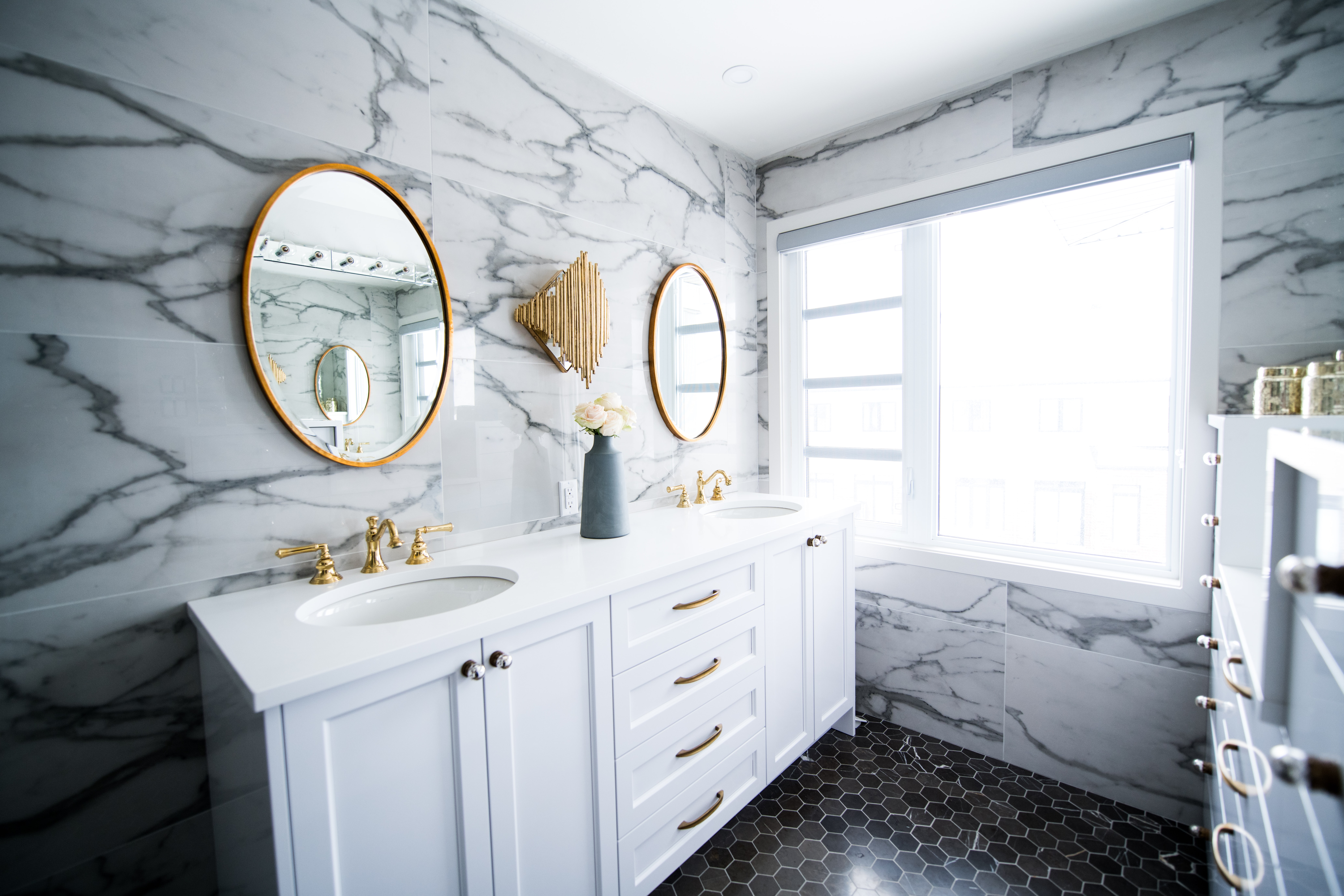 white bathroom cabinets with marble bathroom wall