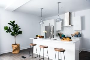 kitchen with white walls and brown stools against a white kitchen island