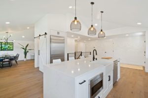 kitchen with brown wood floors and metal pendant lights over kitchen island