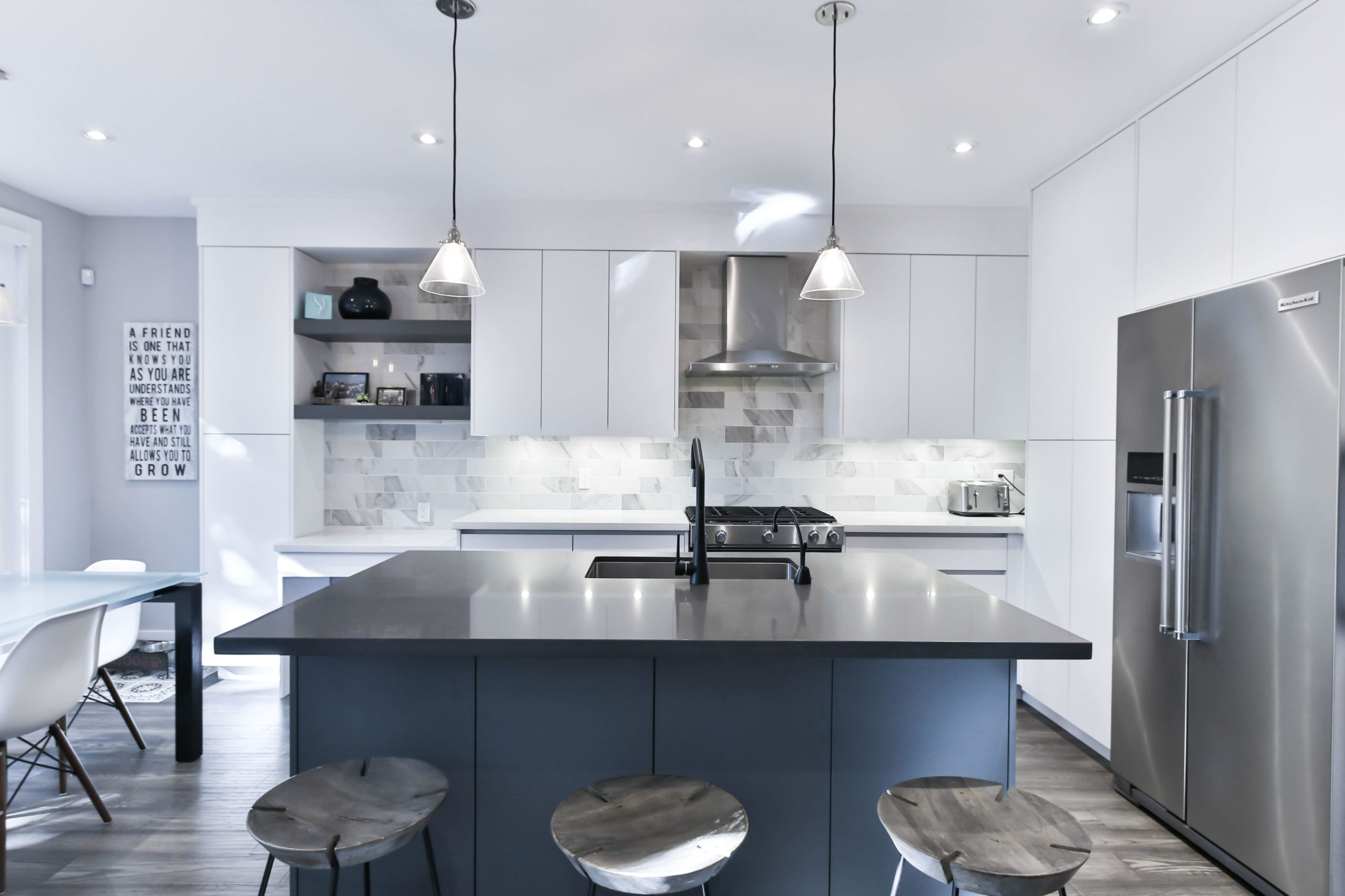 kitchen with black marble island top and white kitchen cabinets