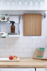 brown cutting board hanging over backsplash